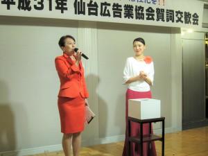 司会進行役の三浦様(左)とクジを引く幸運の女神(右)